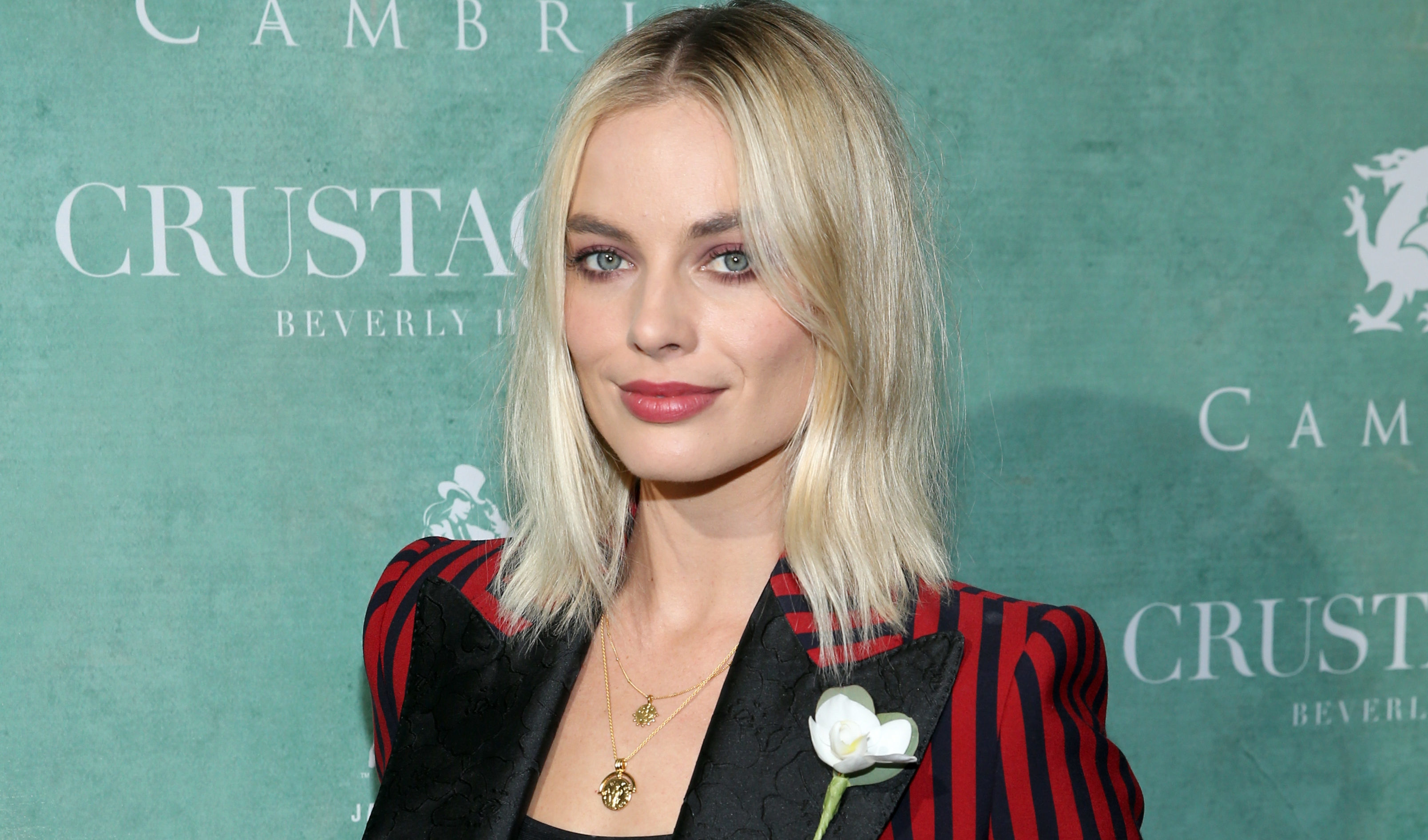 Oscar nominee Margot Robbie wears a white rose to an event in LA on Friday  (Phillip Faraone/Getty Images)
