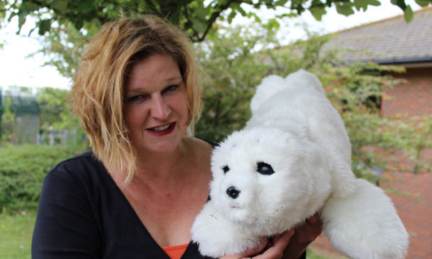 Dr Penny Dodds and a robotic seal. (University of Brighton/PA Wire)