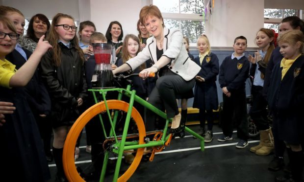 First Minister Nicola Sturgeon tries out a smoothie-making bike at Wellshot Primary School in Glasgow (Jane Barlow/PA)