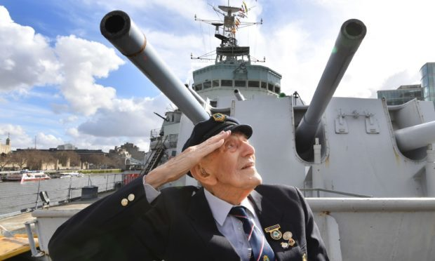 John Harrison aged 104, sits on the foredeck of HMS Belfast in front of gun turret A (John Stilwell/PA)