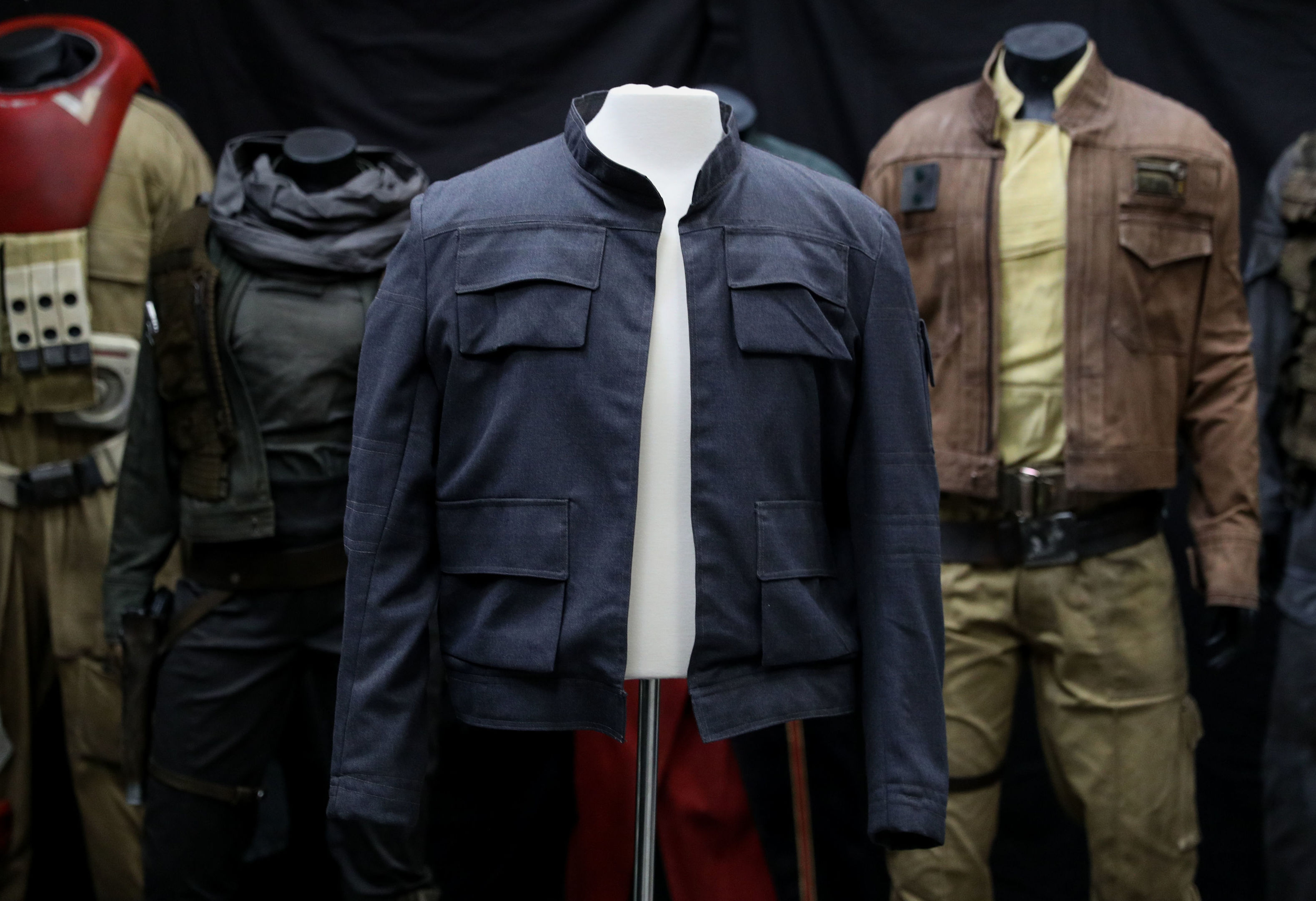 Han Solo's jacket, as worn by Harrison Ford in Star Wars: The Empire Strikes Back on display in front of costumes from Rogue One: A Star Wars Story (Andrew Matthews/PA Wire)