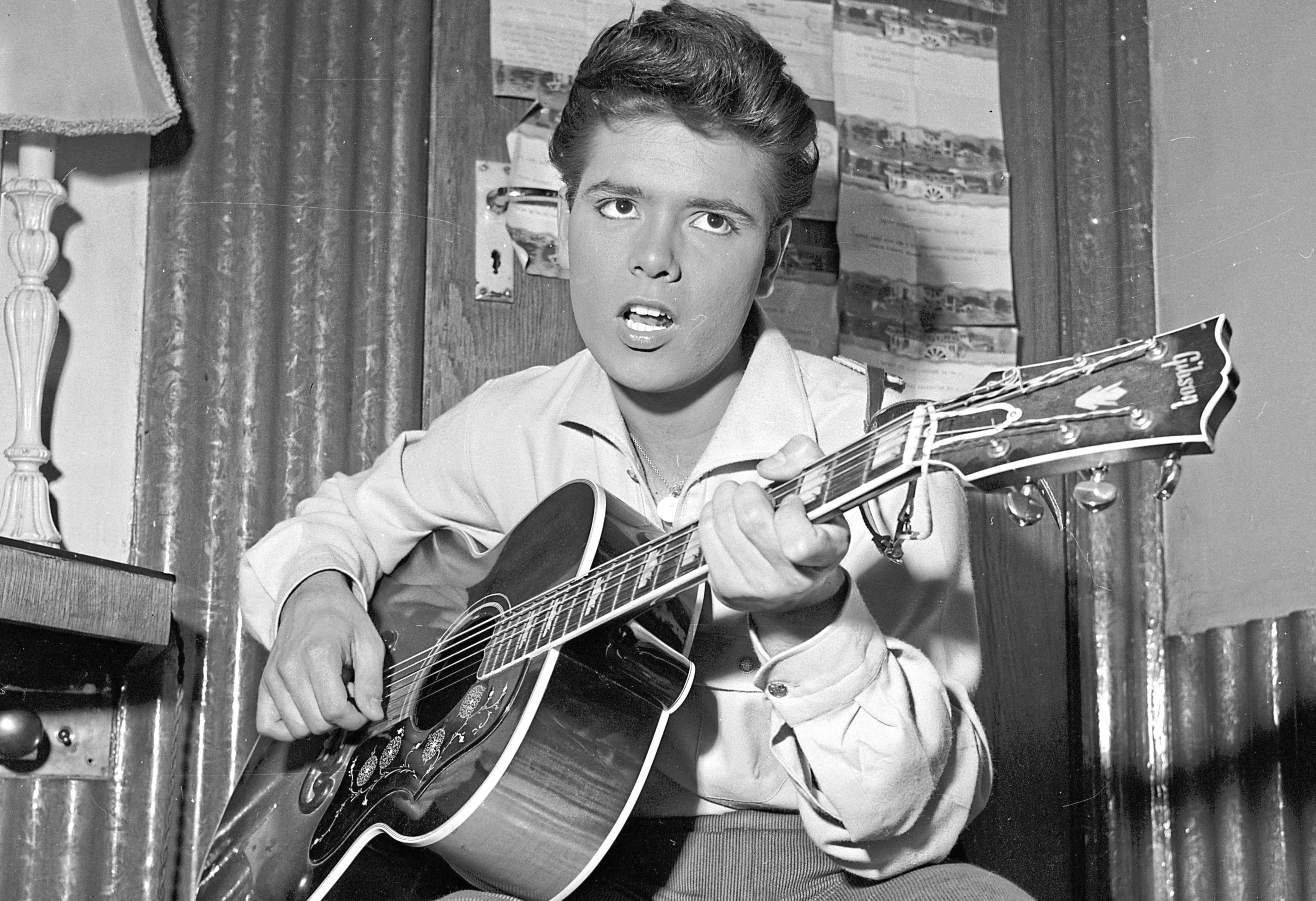 5th August 1960:  English pop star Cliff Richard strums a tune on his trusty guitar before a concert.  (John Pratt/Keystone Features/Getty Images)