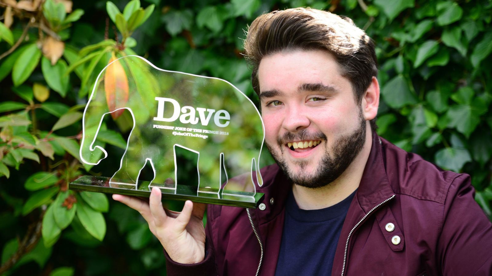Winner Adam Rowe with the 11th Dave's Funniest Joke of the Fringe Award.