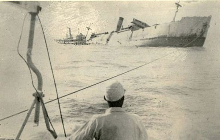 Chinese fishermen watch as the Lisbon Maru lists and sinks beneath the sea