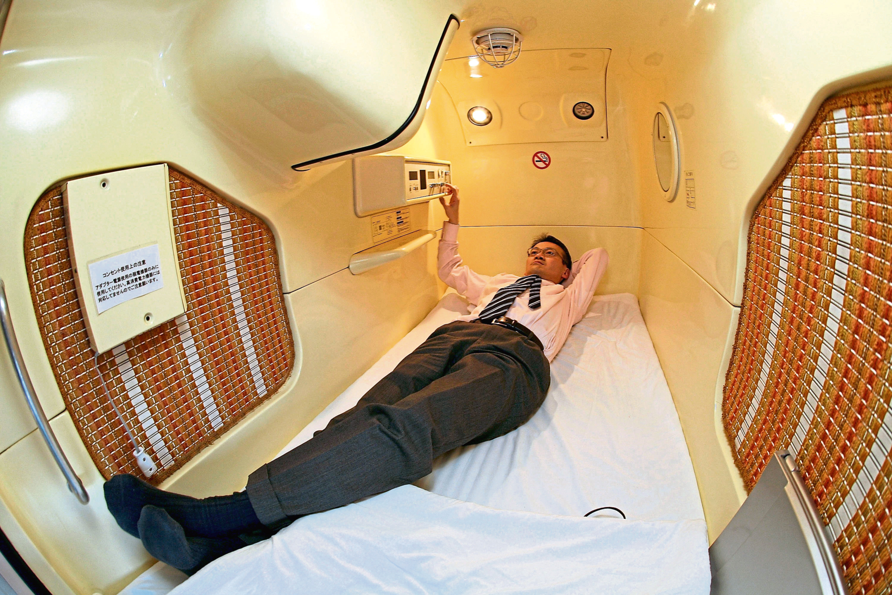 "TOKYO - FEBRUARY 6: A visitor relaxes in a sleeping module at Tokyo's tube Hotel ""Capsule Inn Akihabara"" on February 6, 2007 in Tokyo, Japan. The two-square-meter sleep modules are equipped with a TV, Radio and Wireless LAN and are priced at 3500 yen per night. Uptil recently it has mainly been the office workers who stay at such tube hotels when they cannot go home, but recently they are attracting many foreign travellers due to their Japanese style. (Photo by Koichi Kamoshida/Getty Images)"