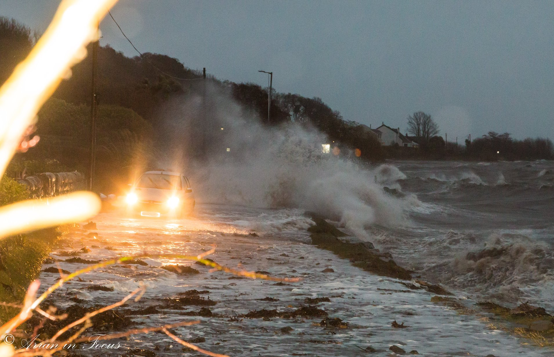 A car avoids surging waves on the Isle of Arran. (Arran in Focus Facebook Page.)