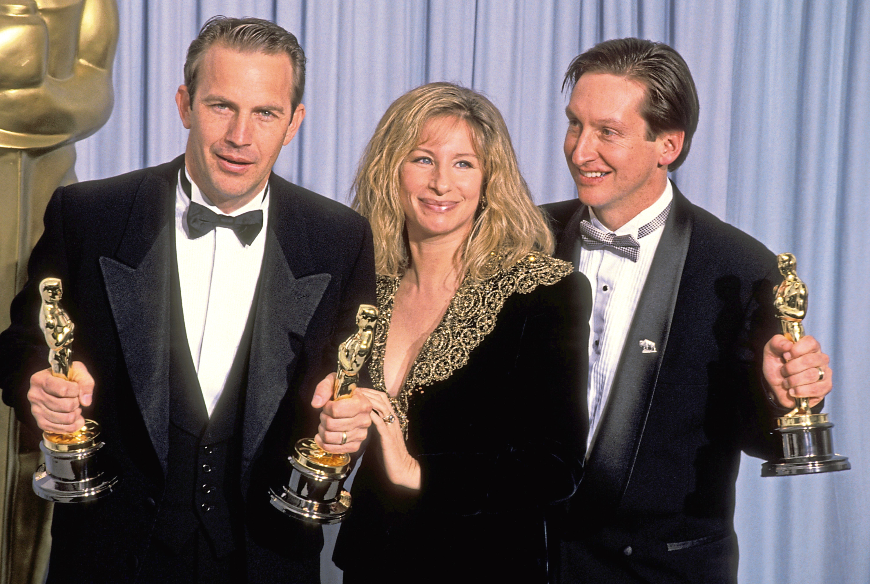 """Kevin Costner and Jim Wilson, winners Best Picture for """"Dances with Wolves,"""" with Barbra Streisand, presenter (center) (Ron Galella/WireImage)"""