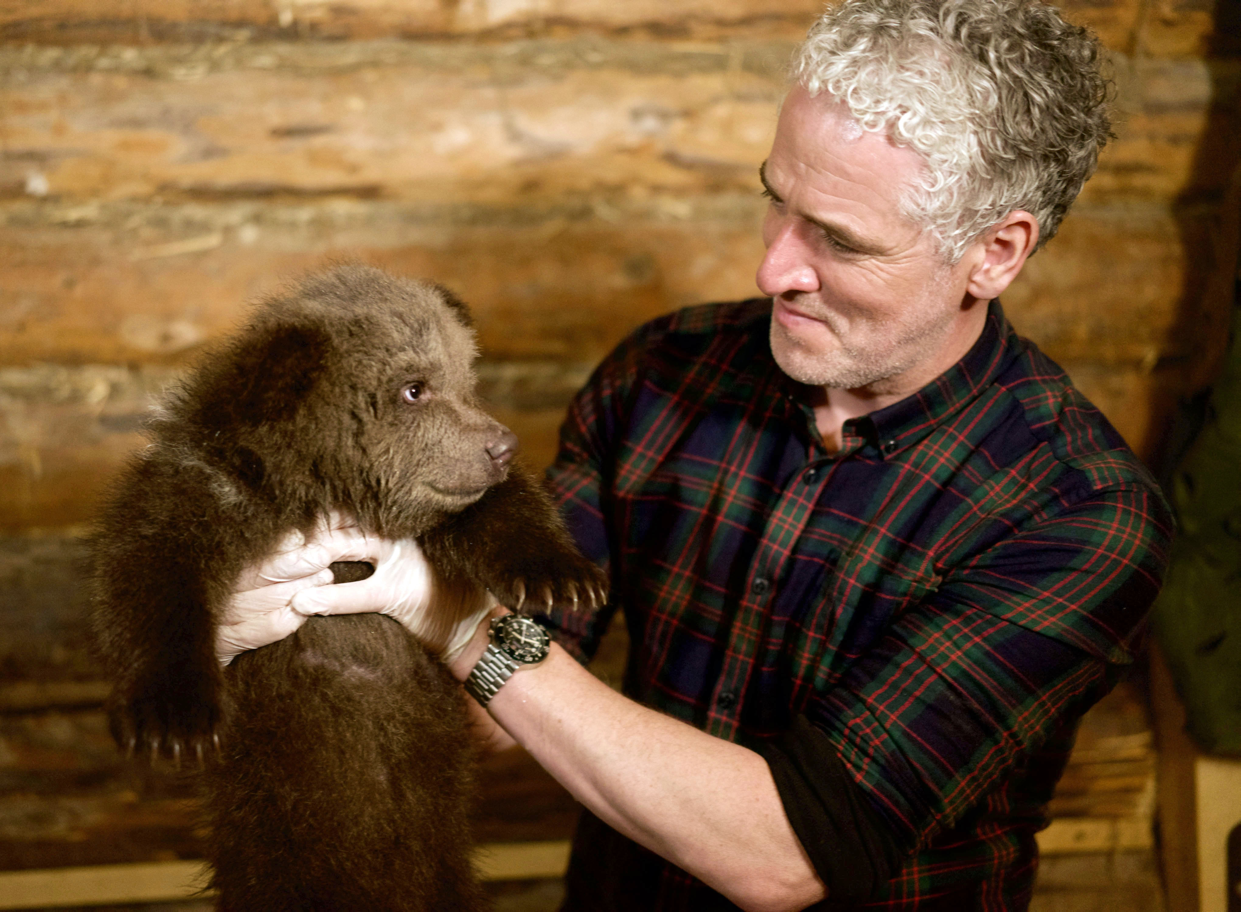 Gordon Buchanan helps to bath an eight-week-old Russian bear cub at the Orphaned Bear Rescue Centre, Bubonitsy, Russia in his new TV series. (Anwar Mamon)