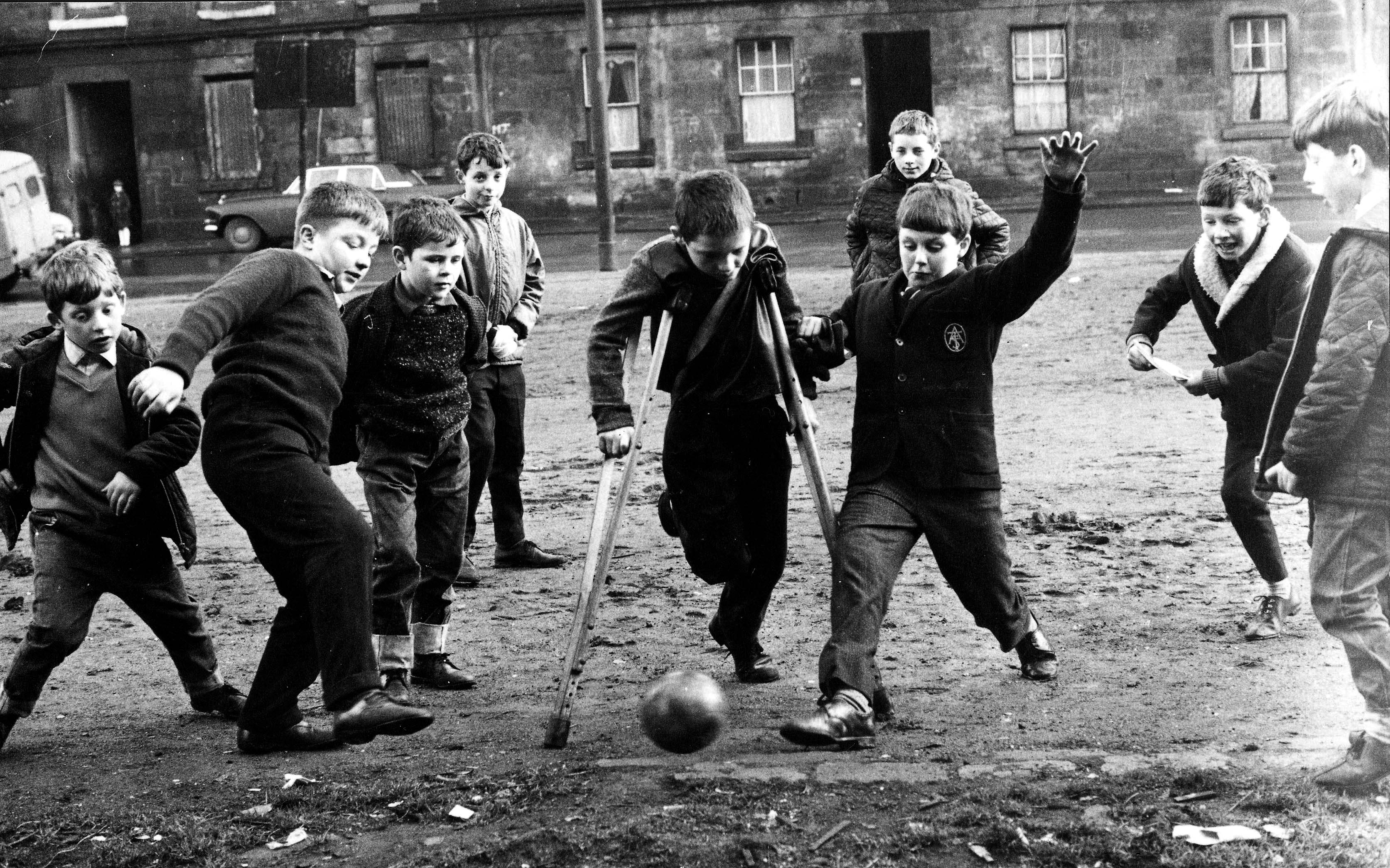 Children kick a football around in the Gorbals, Glasgow in 1967 (Popperfoto/Getty Images)