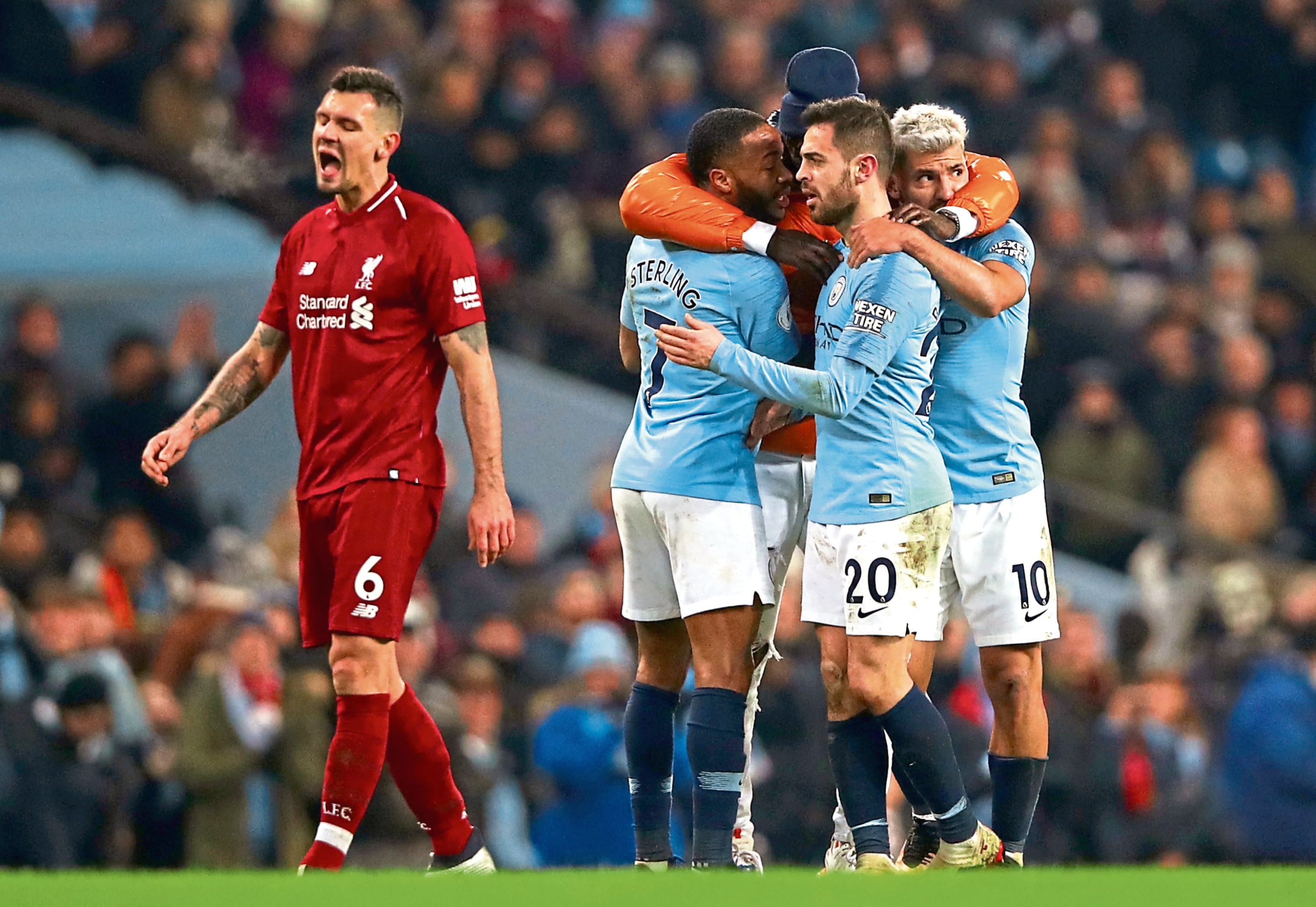 Manchester City's stars celebrate Thursday night's win as Liverpool's Dejan Lovren suffers (Photo by Clive Brunskill/Getty Images)