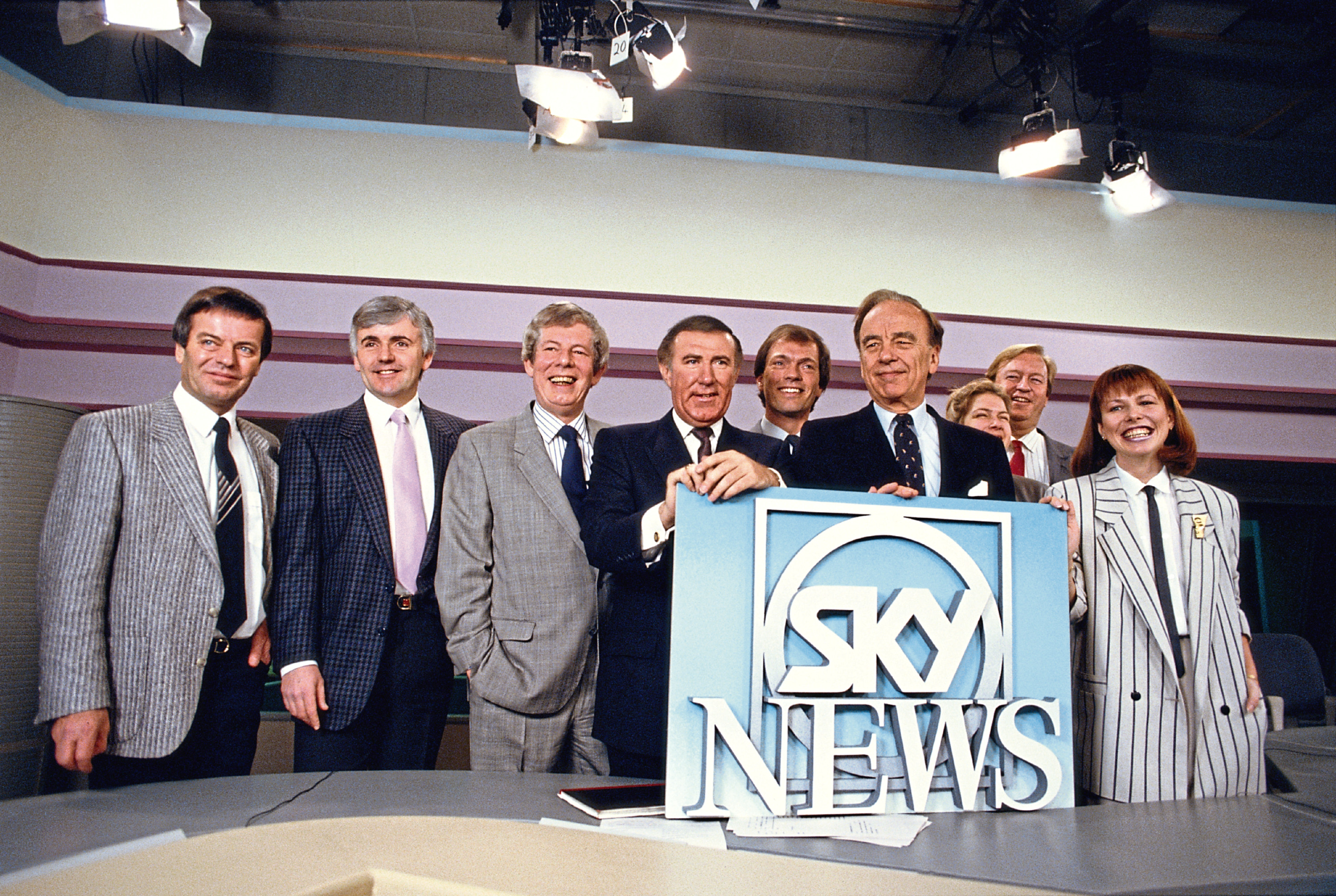 Media magnate Rupert Murdoch and broadcaster Andrew Neil at the launch of Sky TV in London, 5th February 1989. From left to right, Tony Blackburn, Peter Marshall, Derek Jameson, Neil, Alastair Yates, Murdoch, Penny Smith, Bob Friend and Kay Burley.  (Georges De Keerle/Getty Images)