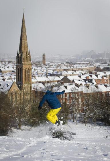 A man snowboarding in Glasgow's Queens Park