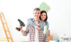 Smiling loving couple doing home renovations, the woman is holding a paint roller and the man is using a drill