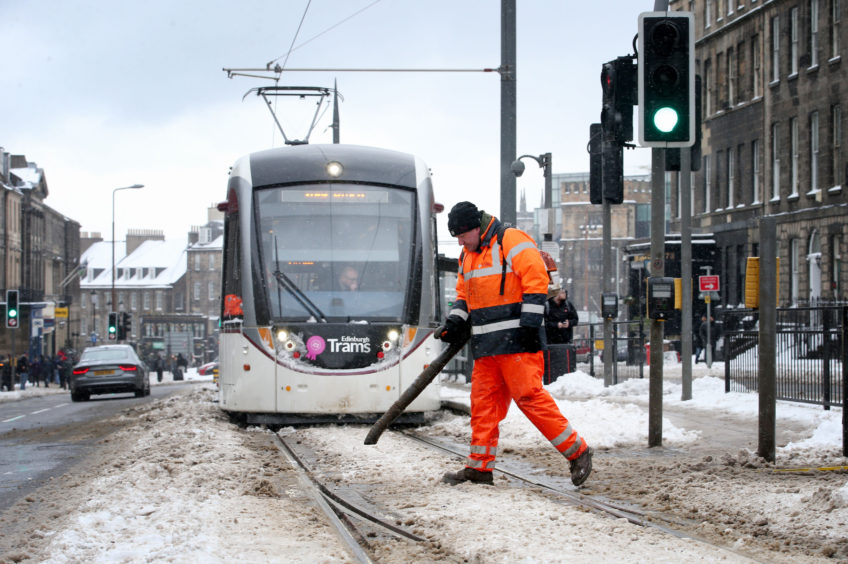 An engineer clears snow and ice from the tram lines along York Place in Edinburgh