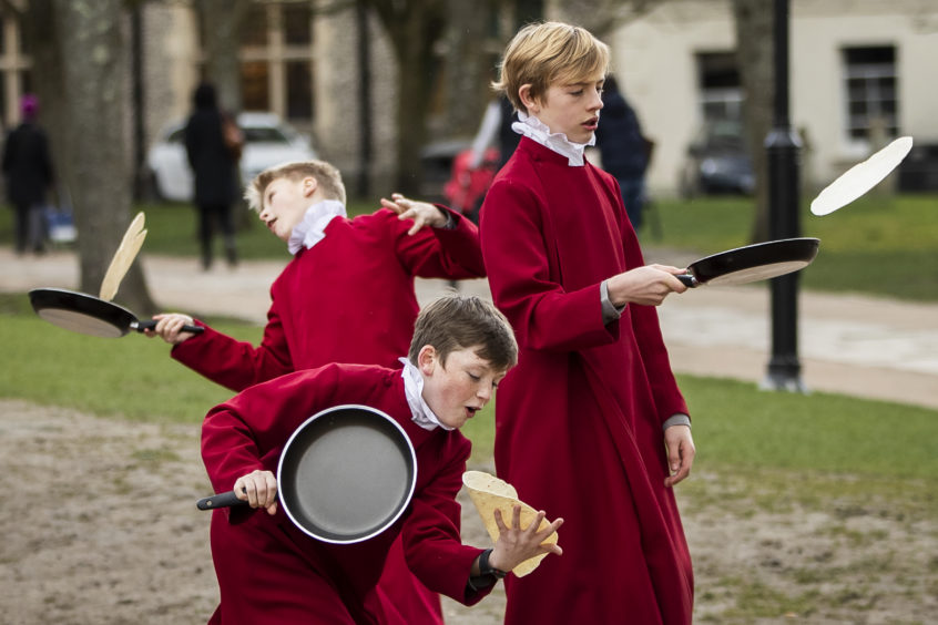 Choristers from Winchester Cathedral joke around in between being posed up for pictures by photographers on March 5, 2019 in Winchester, England. Winchester Cathedral held it's inaugural Shrove Tuesday Pancake day race in the Cathedral grounds today with money raised going to local charities.