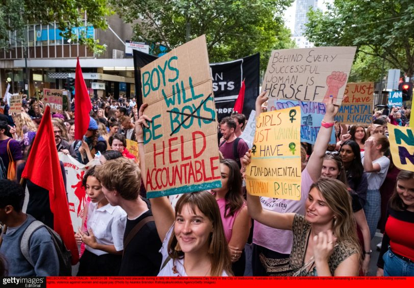 Protestors hold placards during a rally on International Women's Day Rally in the City of Melbourne, Australia on March 08, 2019
