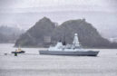 HMS Defender escorted by tugs past Dumbarton Rock