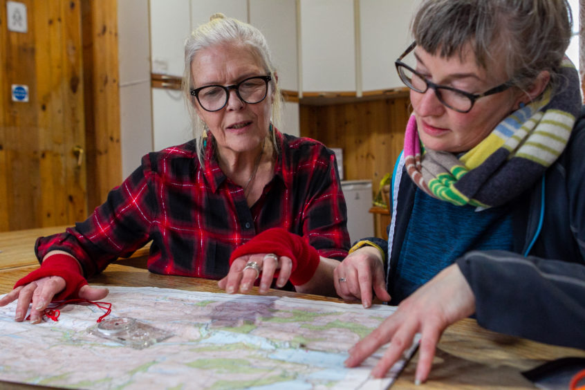 Jan looking at a map with a guest staying at the hostel