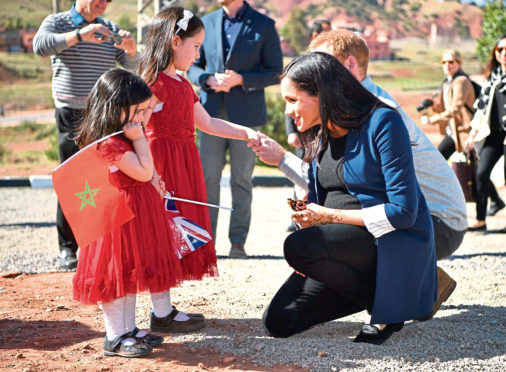 The Duke and Duchess of Sussex talk to two girls the henna design on her hand after a visit to the 'Education For All' boarding house in Asni Town, Atlas Mountains on the second day of her tour of Morocco with the Duke of Sussex.