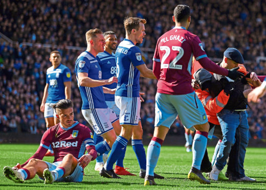 xBIRMINGHAM, ENGLAND - MARCH 10: A fan is wrestled to the ground by a steward after punching Jack Grealish of Aston Villa during the Sky Bet Championship match between Birmingham City and Aston Villa at St Andrew's Trillion Trophy Stadium on March 10, 2019 in Birmingham, England. (Photo by Alex Davidson/Getty Images)