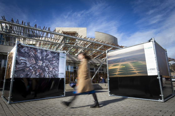 A member of the public admires the large-scale, outdoor photography exhibition showcasing the impact humans have on planet Earth is unveiled today at The Scottish Parliament.