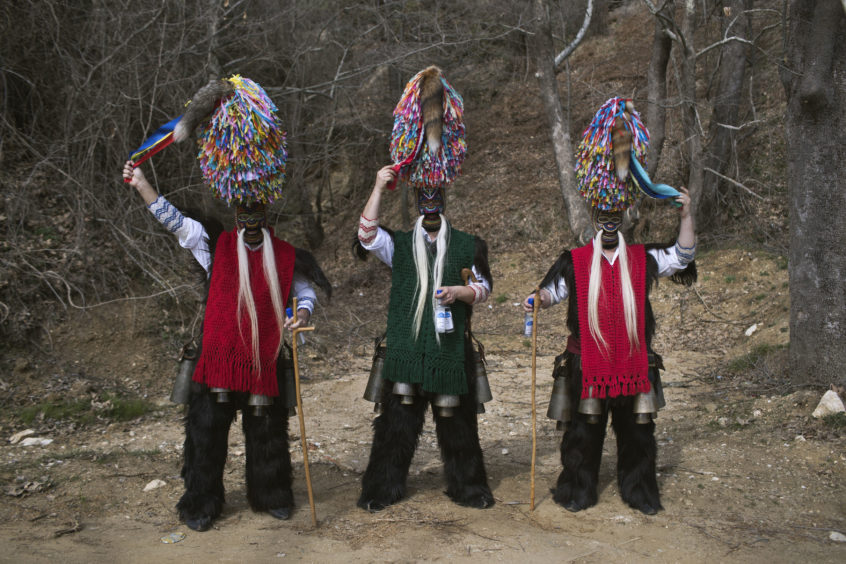 Men wearing goat hides with bells around their waist and masks that include a meter tall, ribbon-covered formation topped with a foxtail, also known as bell wearers, pose for a photo at the village of Sohos, northern Greece as they participate in a Clean Monday festival