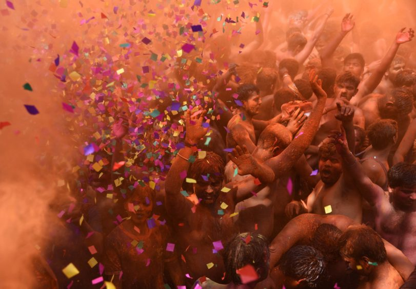 Revellers dance as they celebrate the Hindu Holi festival, or Festival of Colours, in Prayagraj in northern India