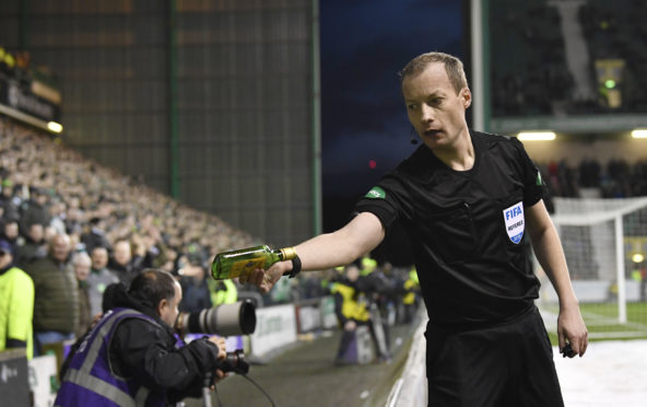 Willie Collum removes a bottle of Buckfast from the pitch after it was thrown at Celtic's Scott Sinclair by Hibs fans