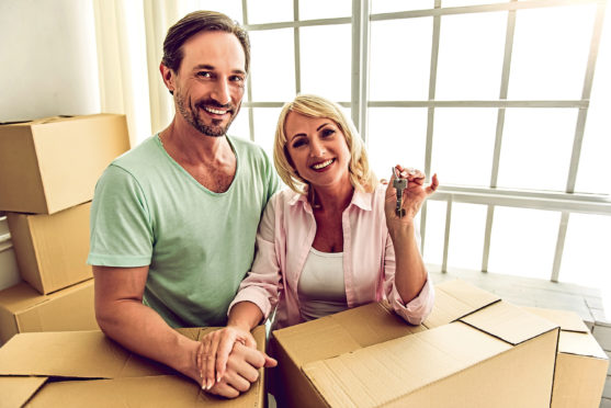 Beautiful mature couple in casual clothes is leaning on the boxes, looking at camera and smiling while moving to the new apartment. Woman is holding keys