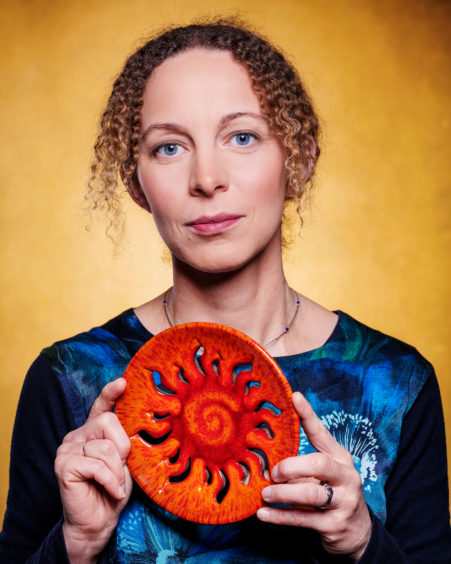 BELGIUM: Prof Ineke DeMoortel FRSE, University of St Andrews, a solar physicist who applies mathematics to understand things in nature. She uses equations describing fluids and magnetic fields to understand more about the solar atmosphere.  Ineke is holding a pottery plate depicting the sun
