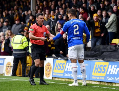 Rangers' James Tavernier spots an object thrown from the Motherwell fans as he goes to take a throw in and hands it to referee Nick Walsh