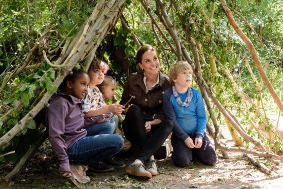 The Duchess of Cambridge making a shelter with local children and Blue Peter presenter Lindsey Russell at Westminster City Council's recreation ground.