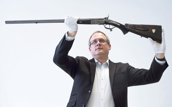 Dr Patrick Watt with rifle gifted to a servant by Queen Victoria