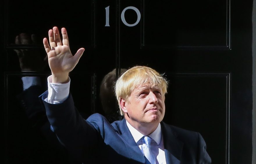 Boris Johnson waves to the media on the steps of 10 Downing Street