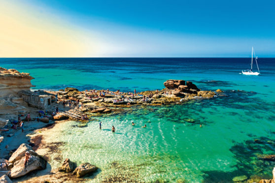 Beatiful cove with fishing piers, rocks and an anchored sailboat, Formentera
