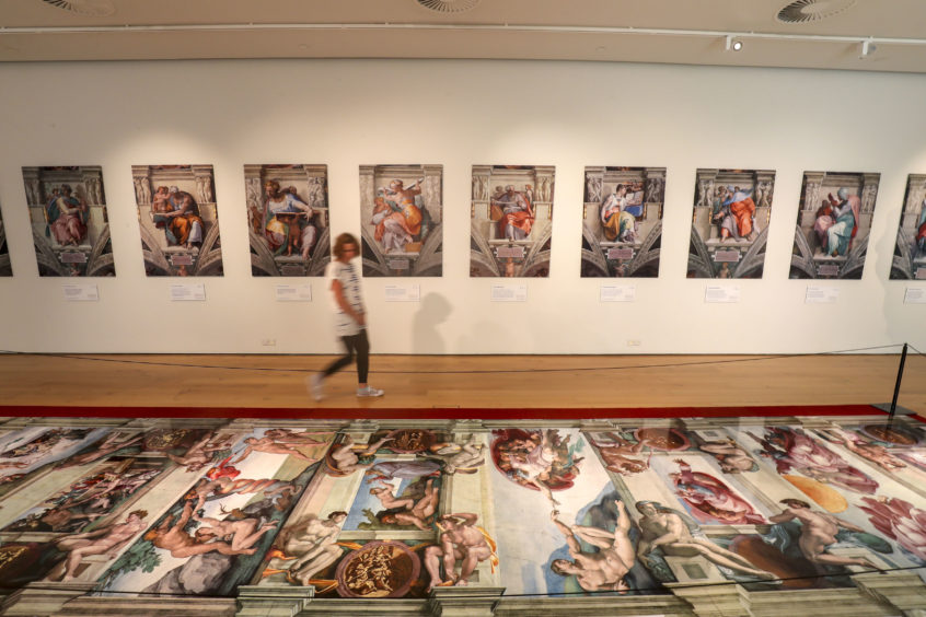 A visitor admires the stunning reproduction of Sistine Chapel frescoes in the UK premiere of Michelangelo exhibition at Winchester Discovery Centre
