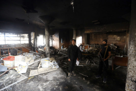 Libyan police check damage at Libyan electoral commission HQ after suicide bombing in Tripoli last year