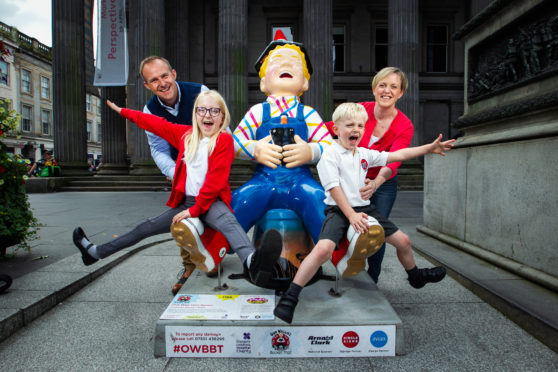 The Simpson Family; parents David and Kerry, with Eve (8), and Hamish (5), standing with the Oor Wullie statue in Royal Exchange Square, Glasgow. The family have spent the summer visiting every statue in Scotland as part of the Bucket Trail.