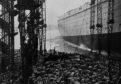 Hats, umbrellas and high-climbing spectators in the massive crowd as King George V and Queen Mary launch the ship