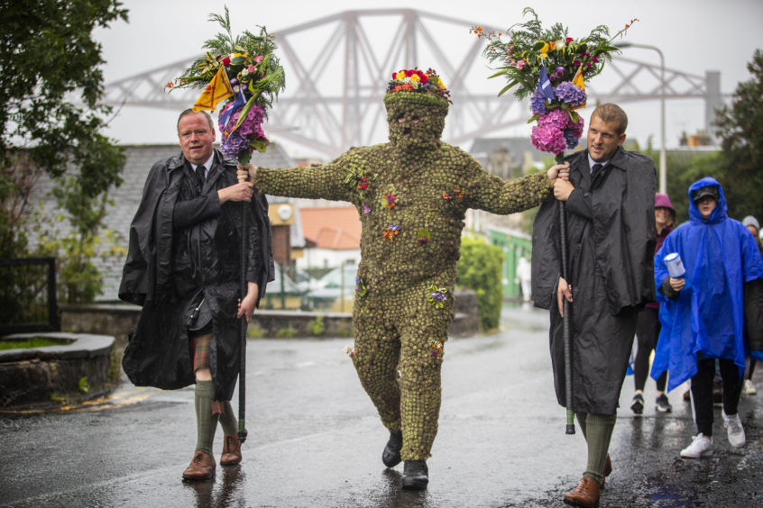 Burryman Andrew Taylor, accompanied by Andrew Findlater (left) and Duncan Thompson (right), meets residents as he parades through the town of South Queensferry