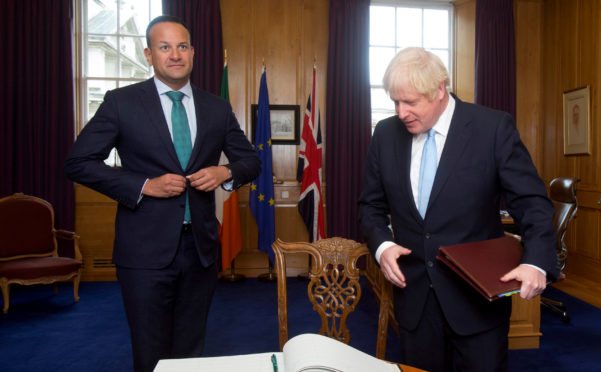 Prime Minister Boris Johnson prepares to sign the visitor's book as Taoiseach Leo Varadkar welcomes him to the Government Buildings during his visit.