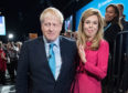 Prime Minister Boris Johnson exits the hall with his girlfriend Carrie Symonds following his keynote speech on day four of the 2019 Conservative Party Conference at Manchester Central on October 2, 2019 in Manchester, England.