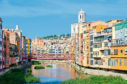View of Eiffel Bridge (Puente Eiffel, or Pont de les Peixateries Velles) across Onyar River, Cathedral and buildings in historical center of Girona, Spain