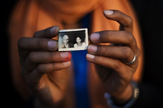 A woman holds a passport photo of lost daughter. An image. A name. A memory. A photograph is often the only thing families have left of their lost daughters..