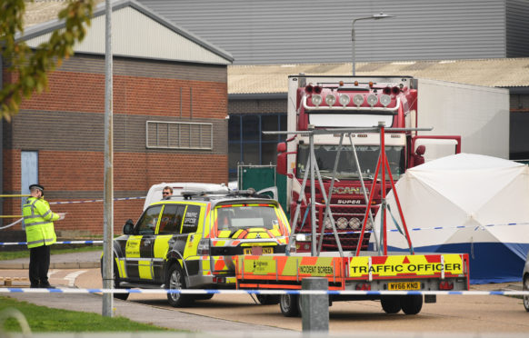 The lorry in which 39 migrants were found dead is secured behind a police cordon in Grays, Essex, after grim discovery on Wednesday