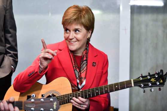 First Minister Nicola Sturgeon holds a guitar as she visits Dalkeith Community Hub