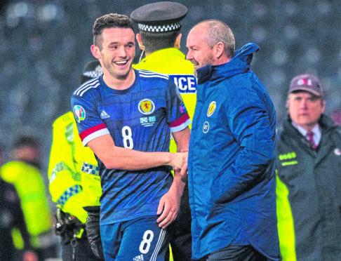 Scotland's John McGinn (L) shakes hands with manager Steve Clarke during the UEFA European Championship Qualifier between Scotland and Kazakhstan at Hampden Park, on November 19, in Glasgow, Scotland.