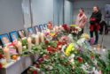 People pay tribute near portraits of crew members of the Ukraine International Airlines Flight PS752 at Boryspil International Airport in Kiev, Ukraine
